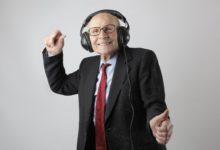 cheerful elderly man listening to music in headphones